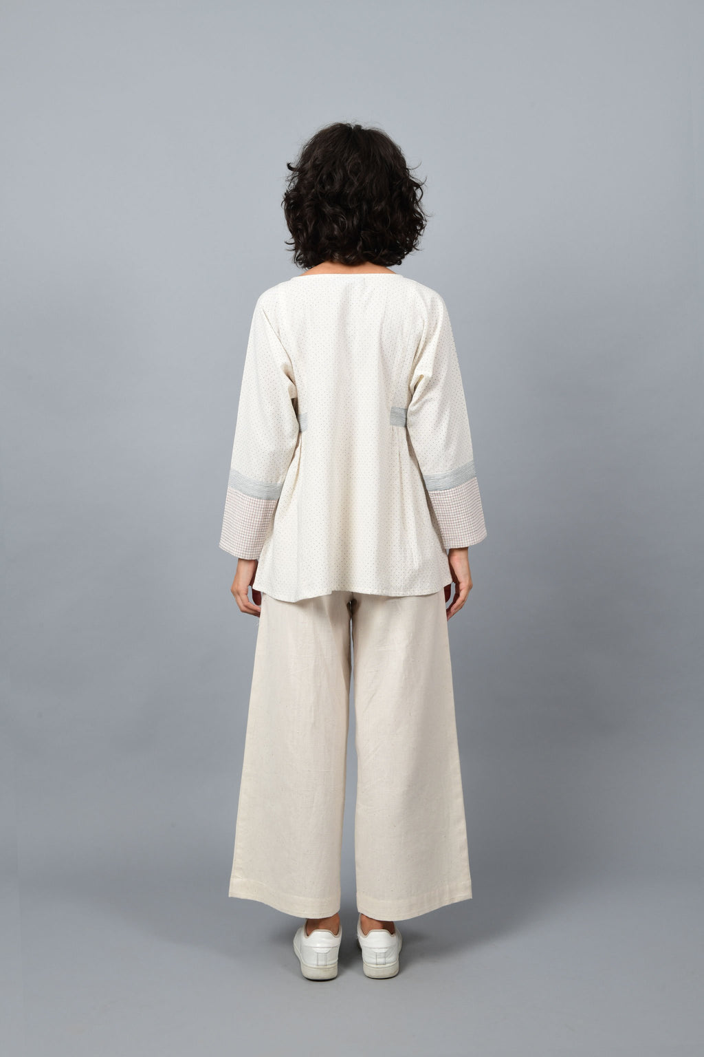 Back of the Model wearing Dolman sleeve side gather khadi handspun handwoven cotton top in natural off-white color with blue dots and blue stripes on the sleeves teamed with off-white palazzos and white sneakers