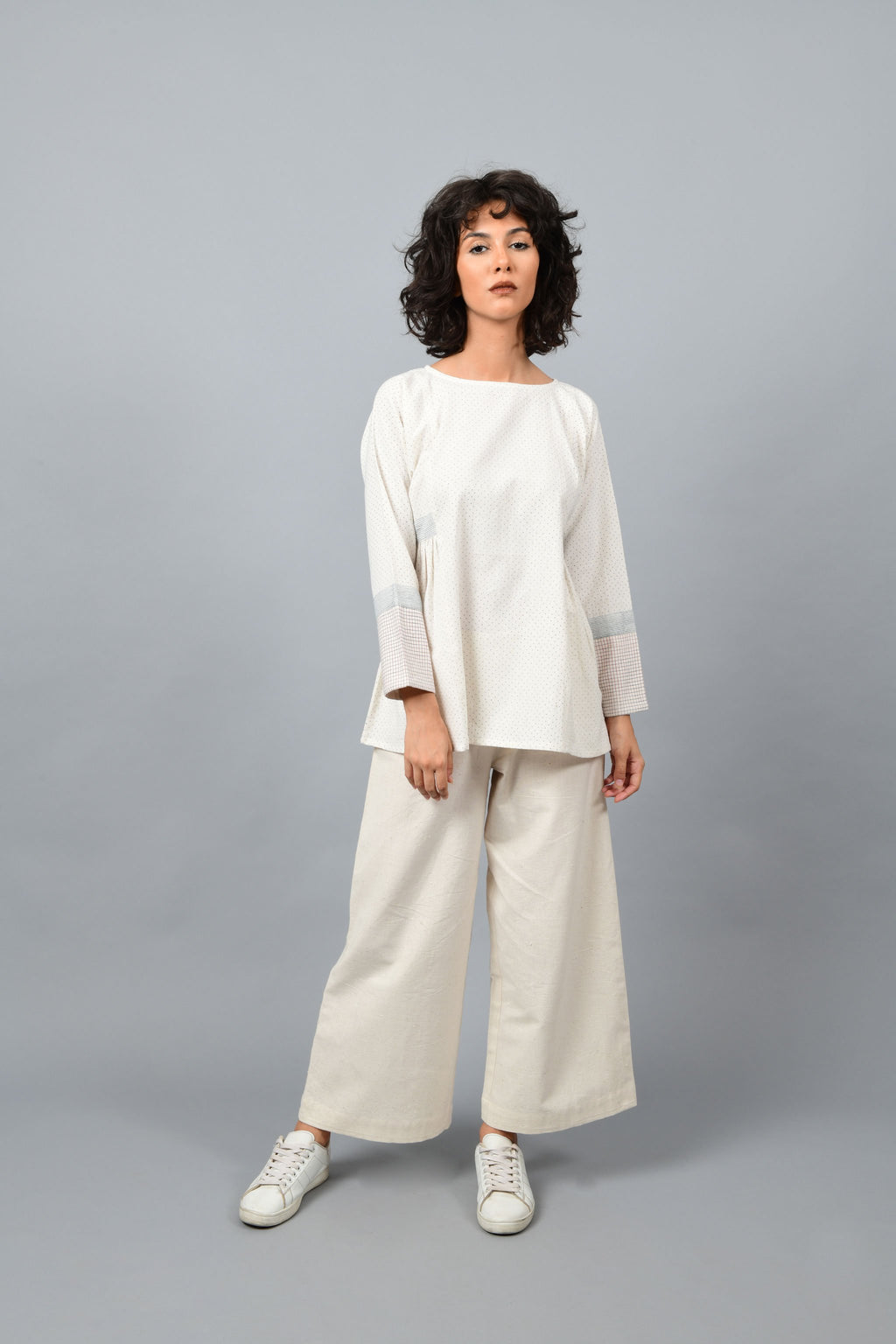 Model wearing Dolman sleeve side gather khadi handspun handwoven cotton top in natural off-white color with blue dots and blue stripes on the sleeves teamed with off-white palazzos and white sneakers