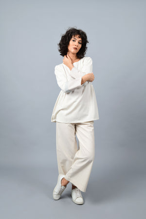 A Model casually posing wearing Dolman sleeve side gather khadi handspun handwoven cotton top in natural off-white color with blue dots and blue stripes on the sleeves teamed with off-white palazzos and white sneakers