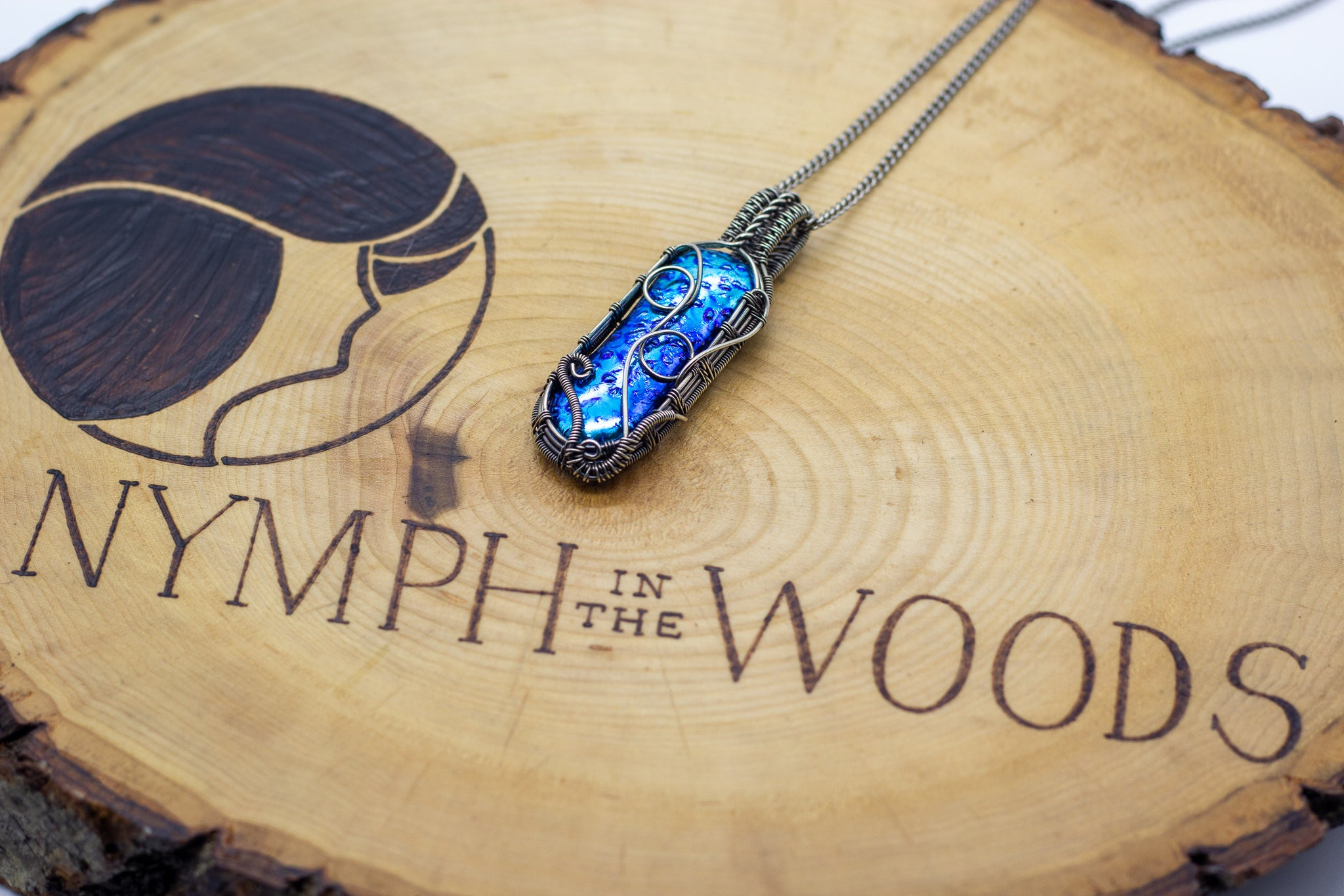 handmade pendant with bright blue fused glass and sterling silver wire wrapping