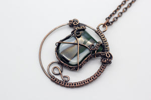 handmade circular pendant with copper wire wrapping and green and white fused glass