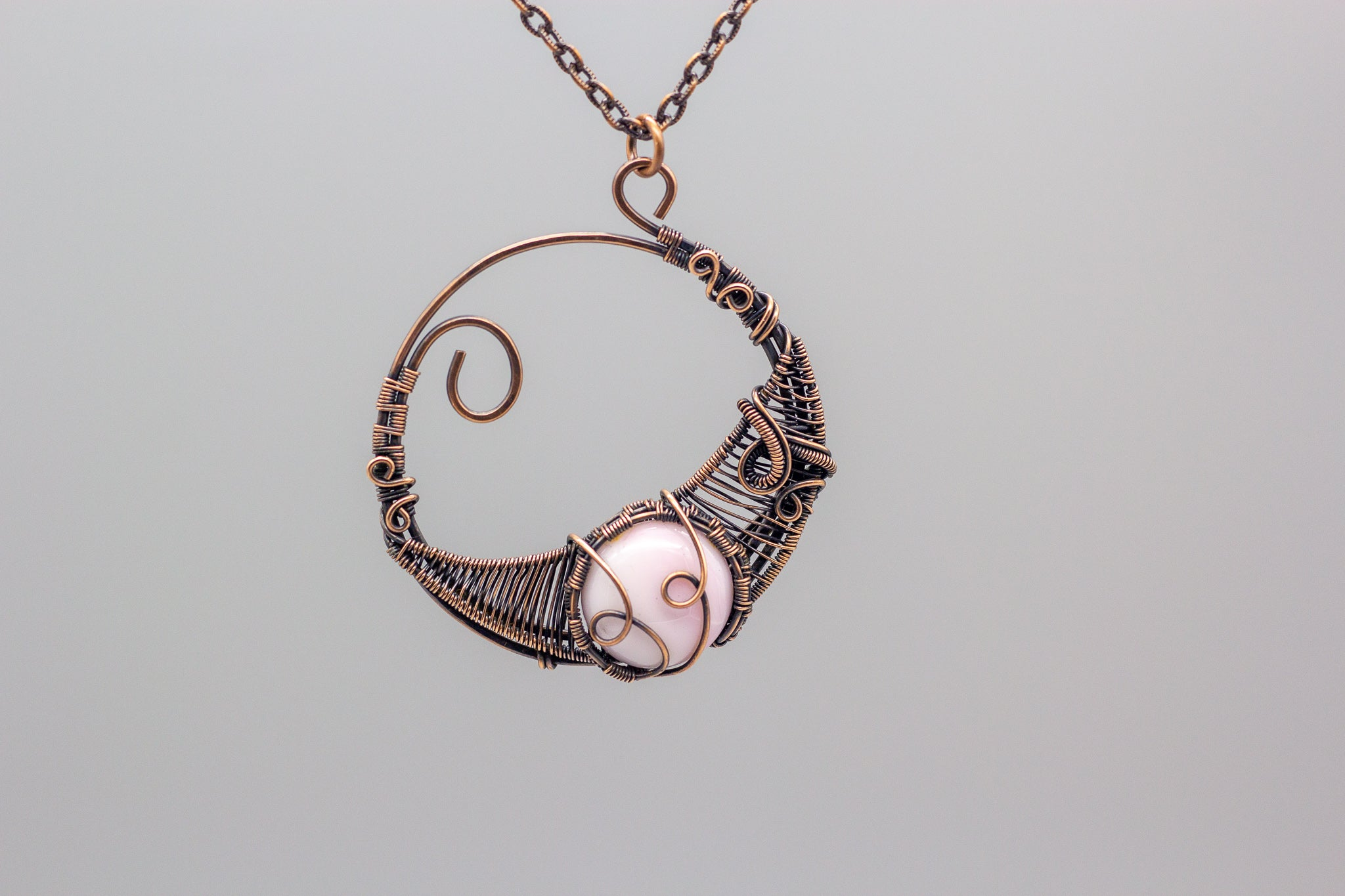 handmade circular pendant with copper wire wrapping and pink fused glass accent