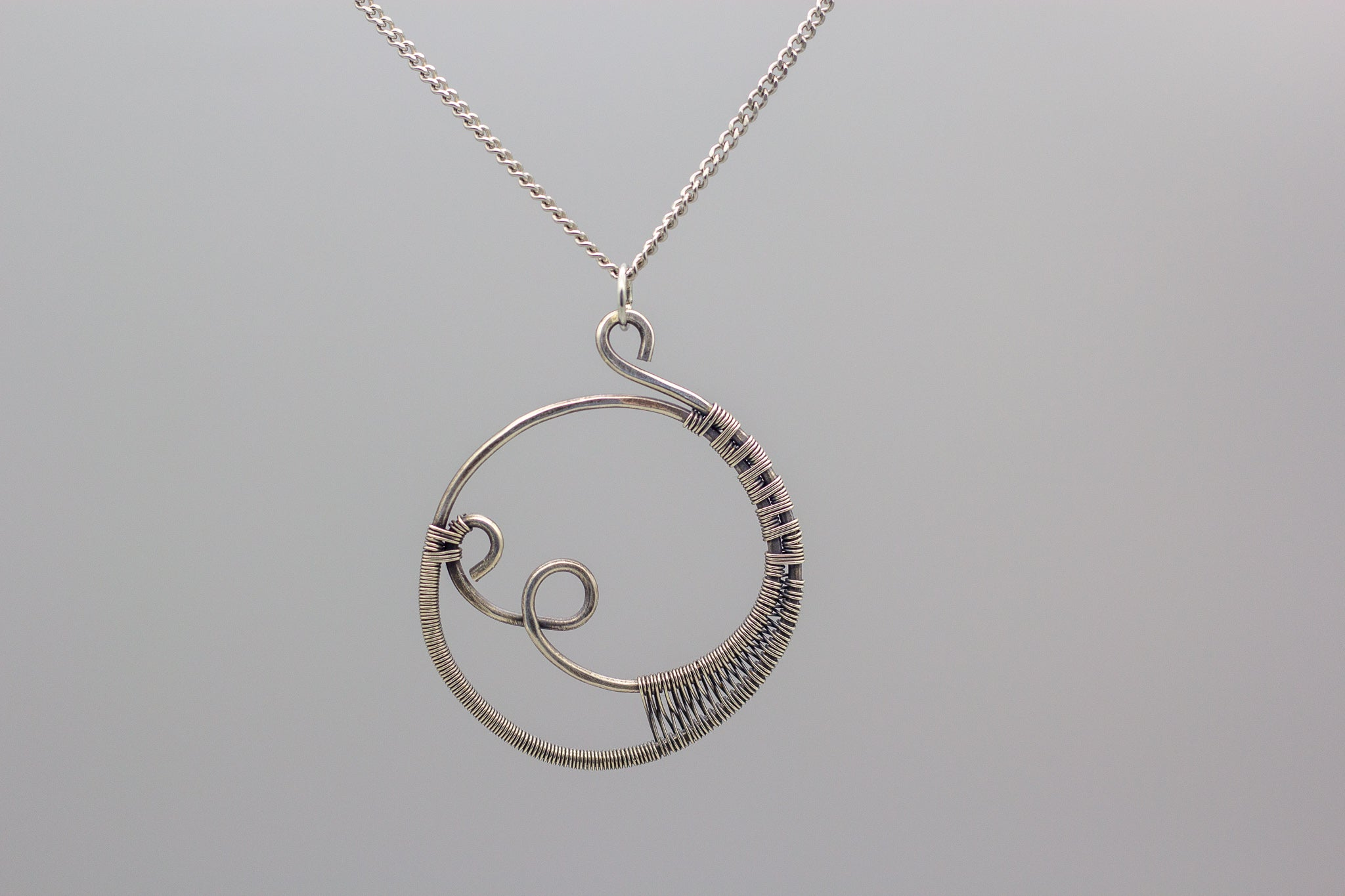 handmade circular pendant with sterling silver wire wrapping
