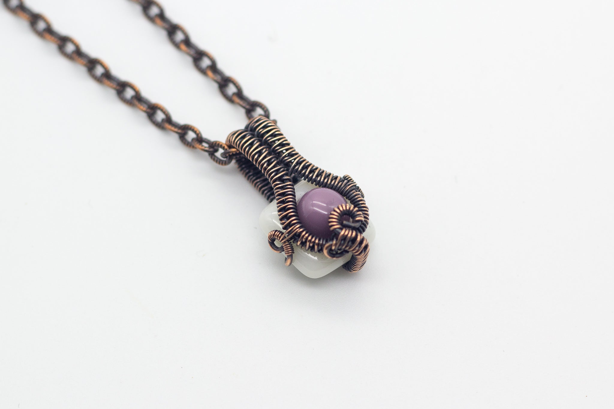 Small handmade pendant with purple and white fused glass and copper wire wrapping