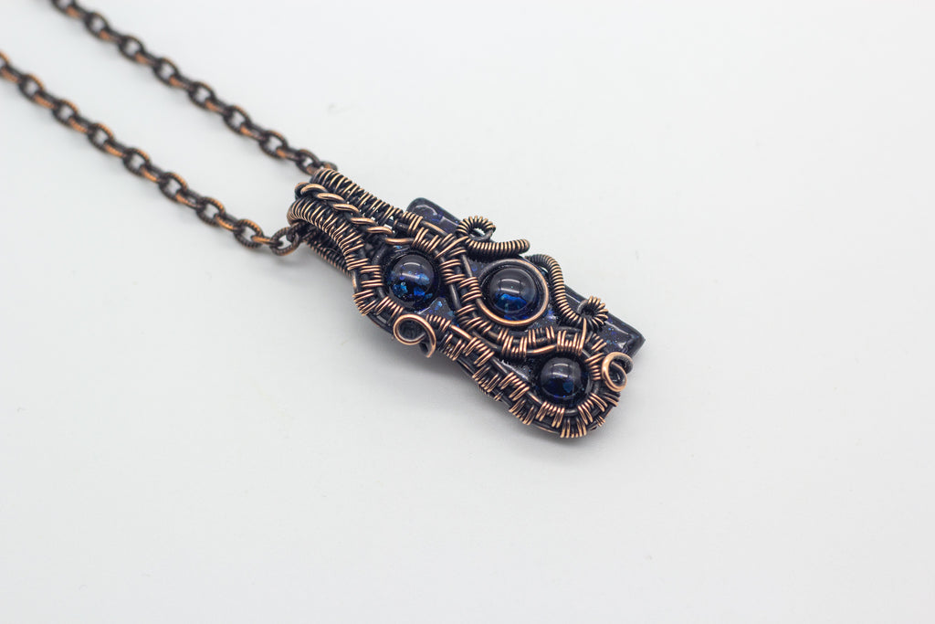 Handmade abstract pendant with glittery blue fused glass and copper wire wrapping