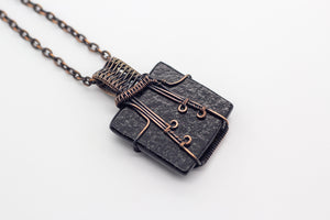 handmade pendant with glittery black fused glass and copper wire wrapping
