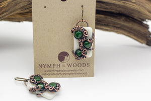 Handmade earring with white and dark green fused glass and copper wire wrapping