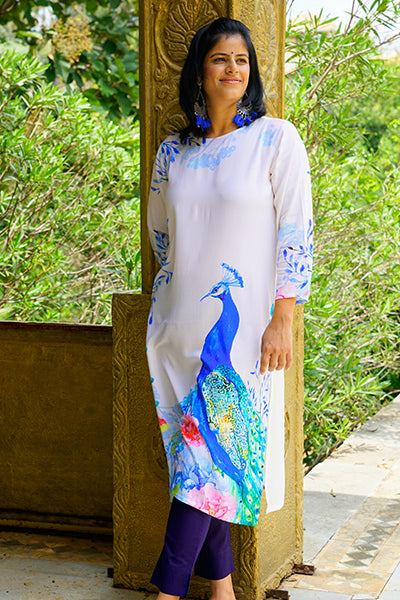 Prakriti Byogi Collection. This is a white kurti with peacock print. It is a rayon straight kurti.