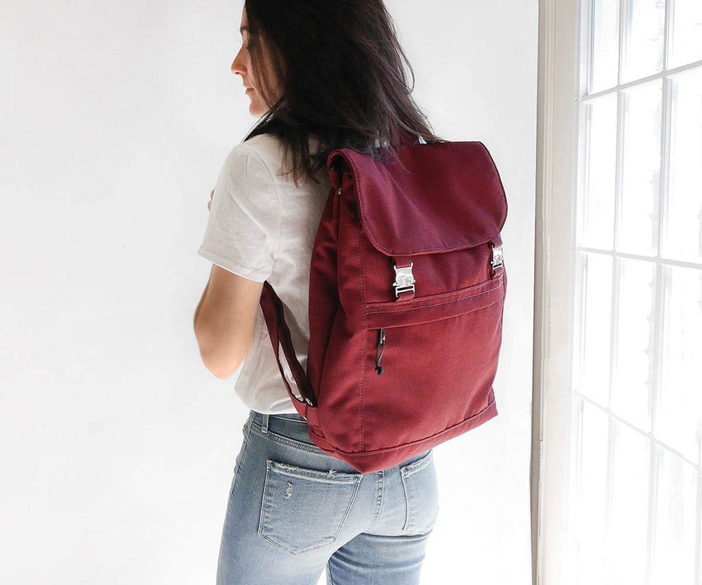 minimal burgundy canvas travel backpack with modern buckles