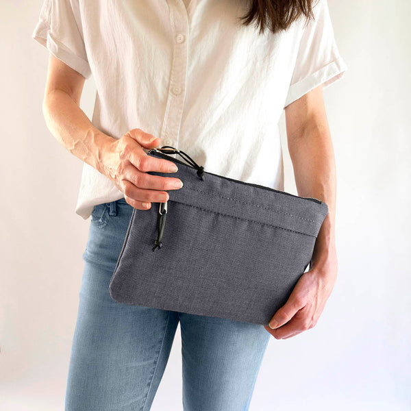 woman holding flat clutch in charcoal gray