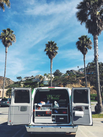 Kitcen area of Escape Campervan with California palm trees in the background