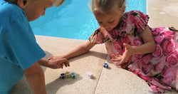 2 kids playing football dice by the pool on summer holiday