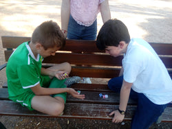 Two 9 year old boys playing a Football Dice match on a park bench