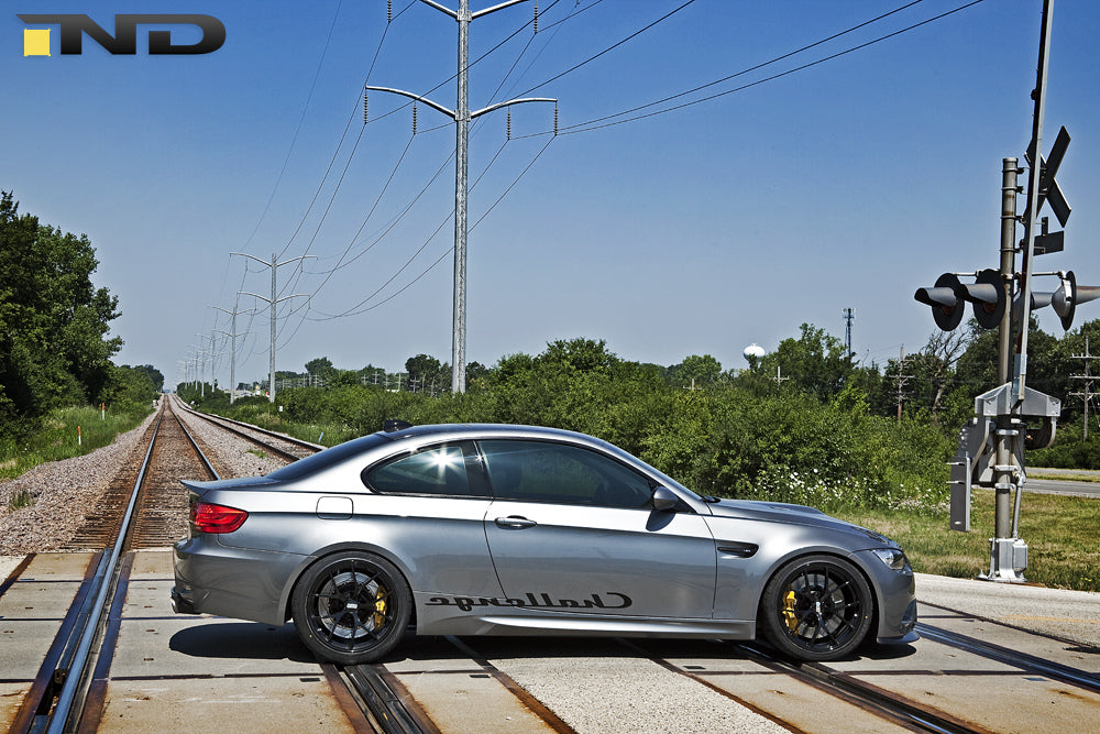 Silver BMW driving over train tracks outside