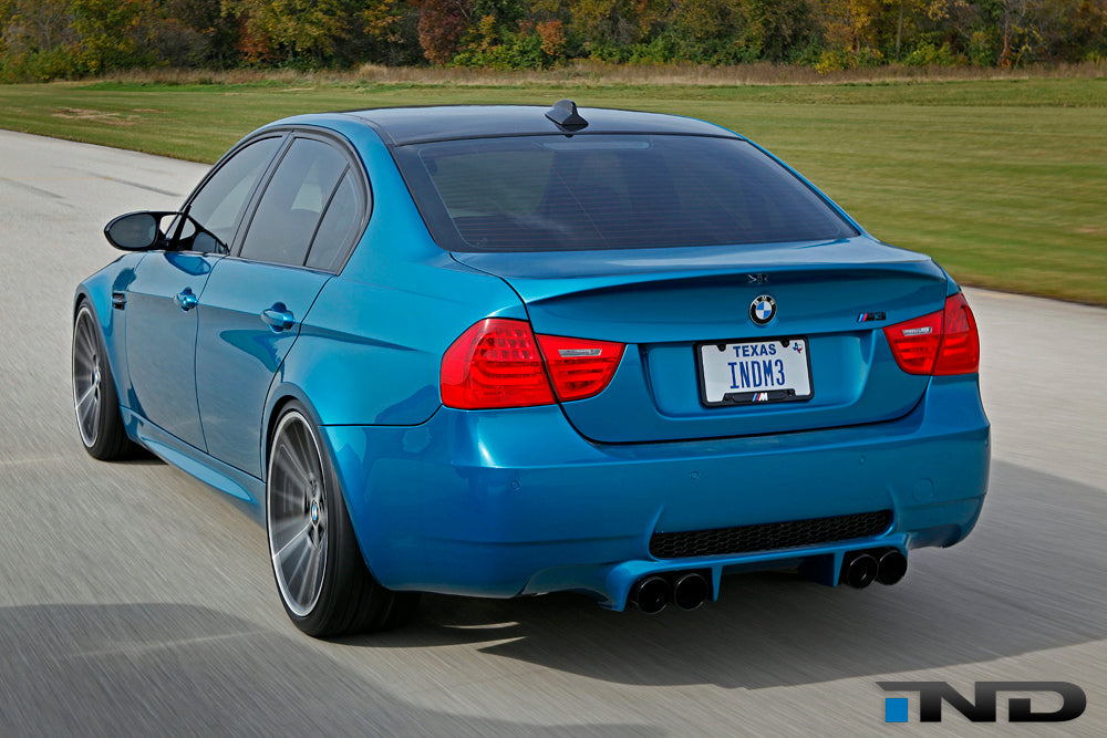 Blue BMW with carbon fiber race trunk driving outside