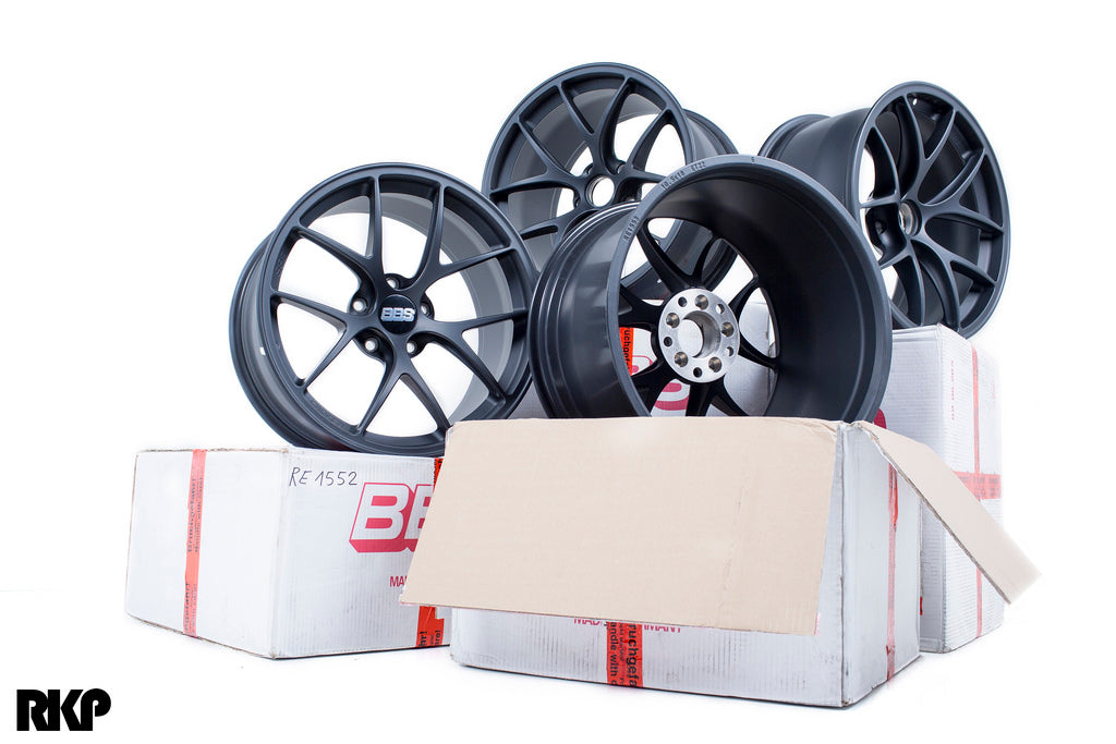 4 black shiny BBBs wheels posed on cardboard boxes