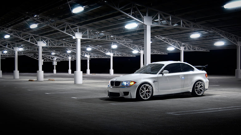 Bright White BMW in a dark parking lot outside