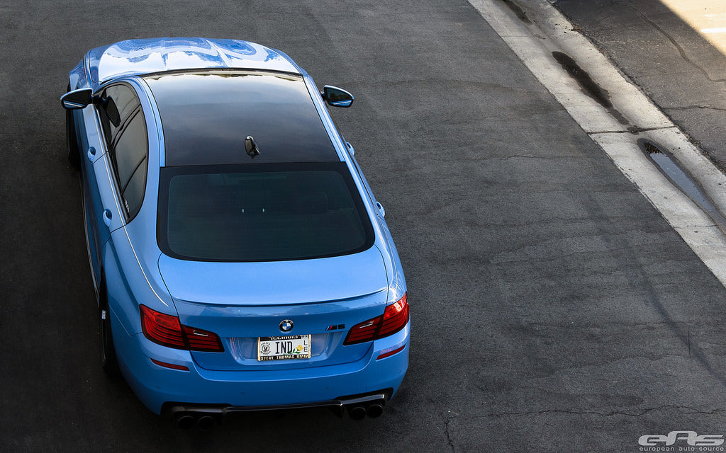 Bird's eye view of blue BMW driving down the road