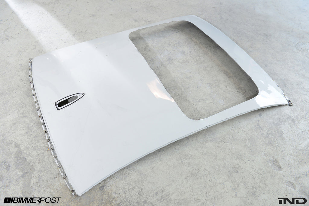Detached white BMW roof on the floor