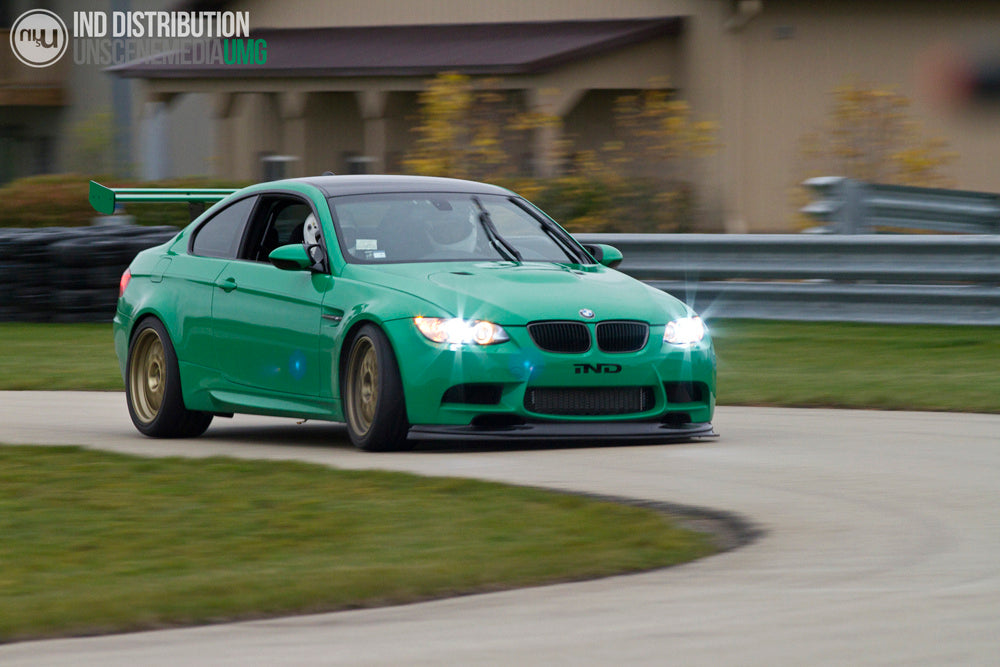 Green BMW driving around a bend outside