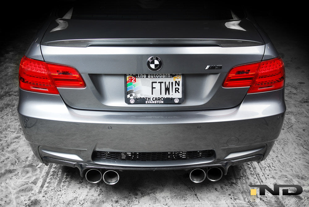 Rear of silver BMW with black carbon fiber race trunk