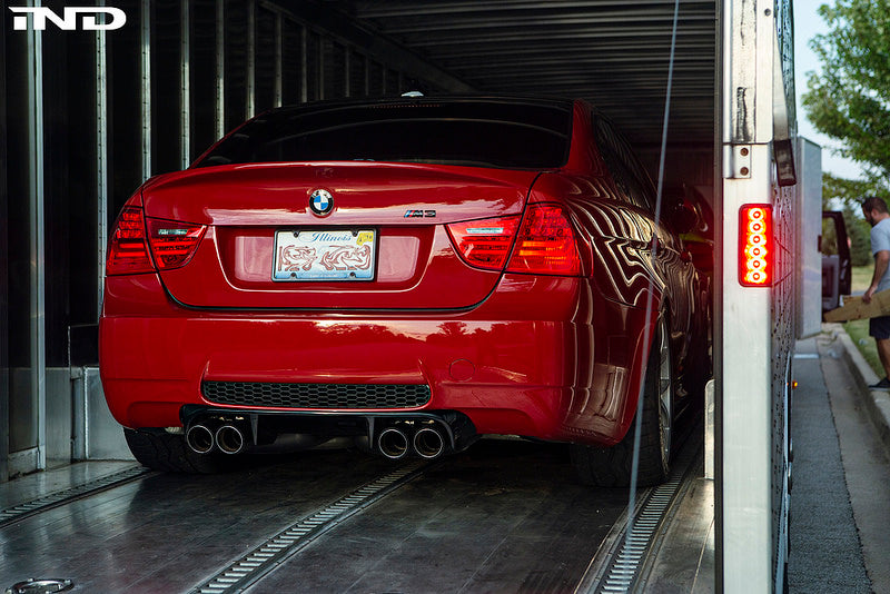 Red BMW loaded in the back of a truck