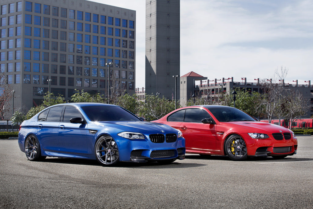 A blue BMW and a red BMW side by side in front of the city