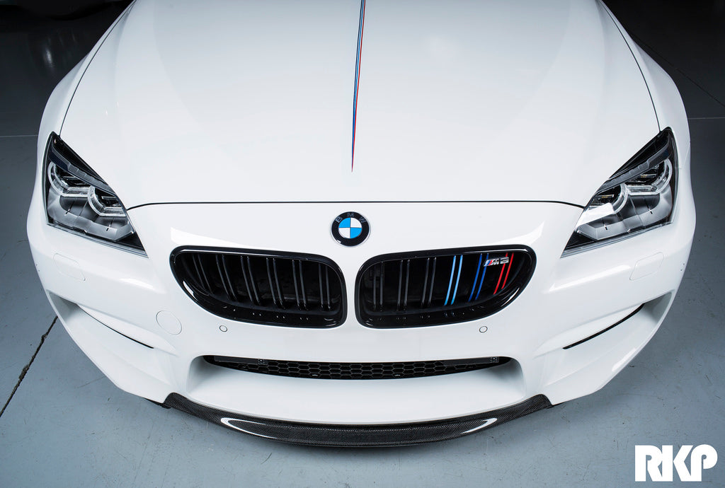 Front of white BMW in a dark parking garage