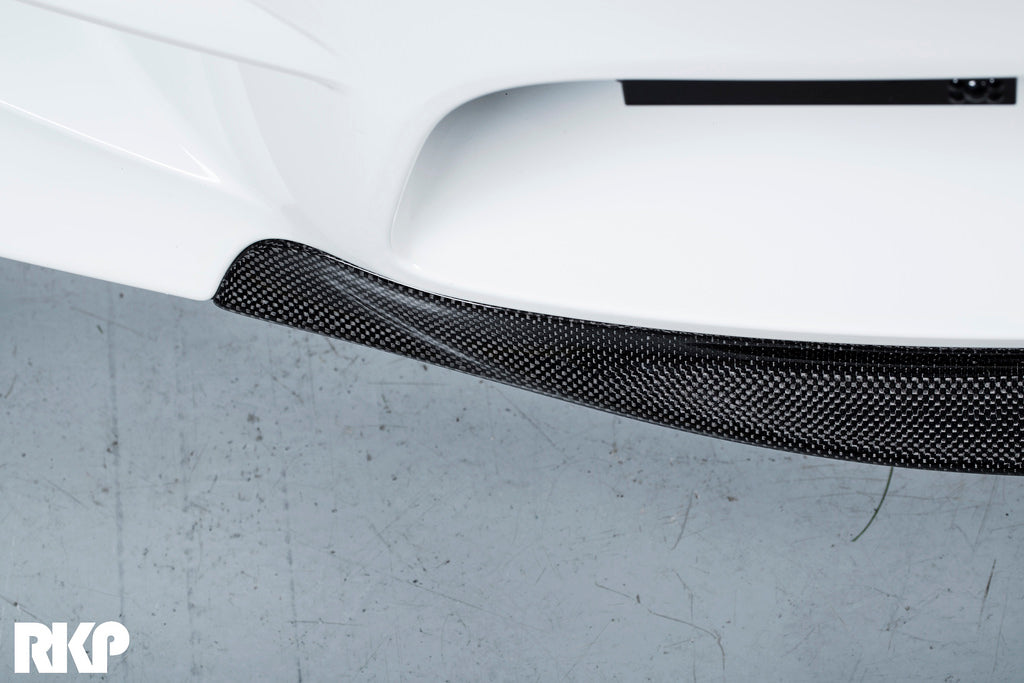 Top down view of black carbon fiber detail on a white BMW