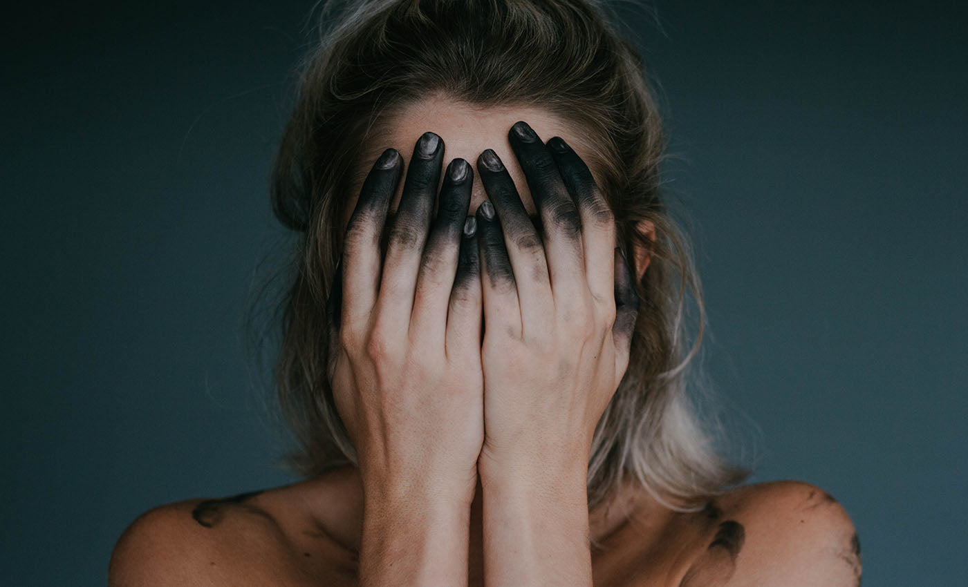Woman with activated charcoal fingers on face