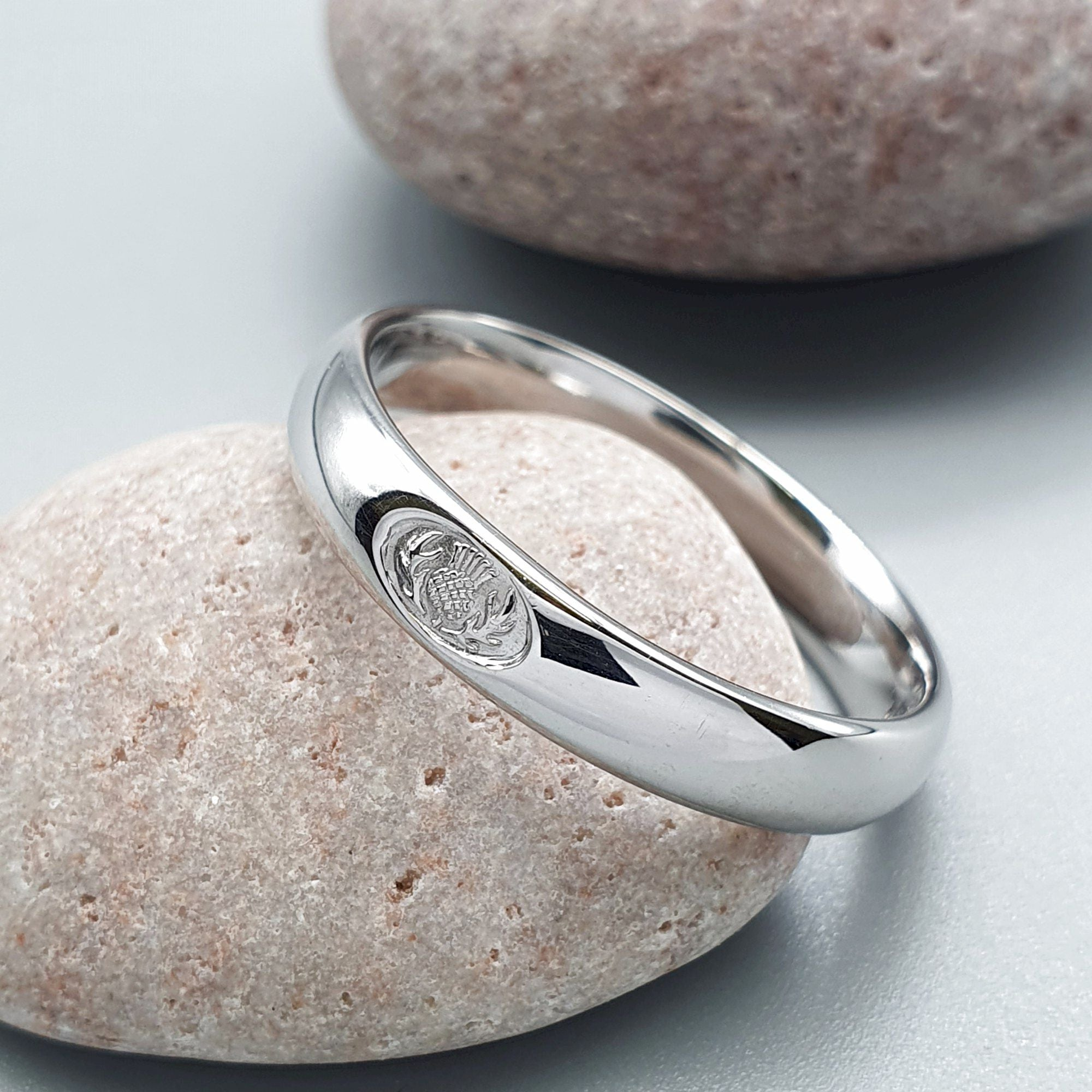 It is a picture of Wedding ring 50mm to 50mm Scottish Thistle white gold narrow band.