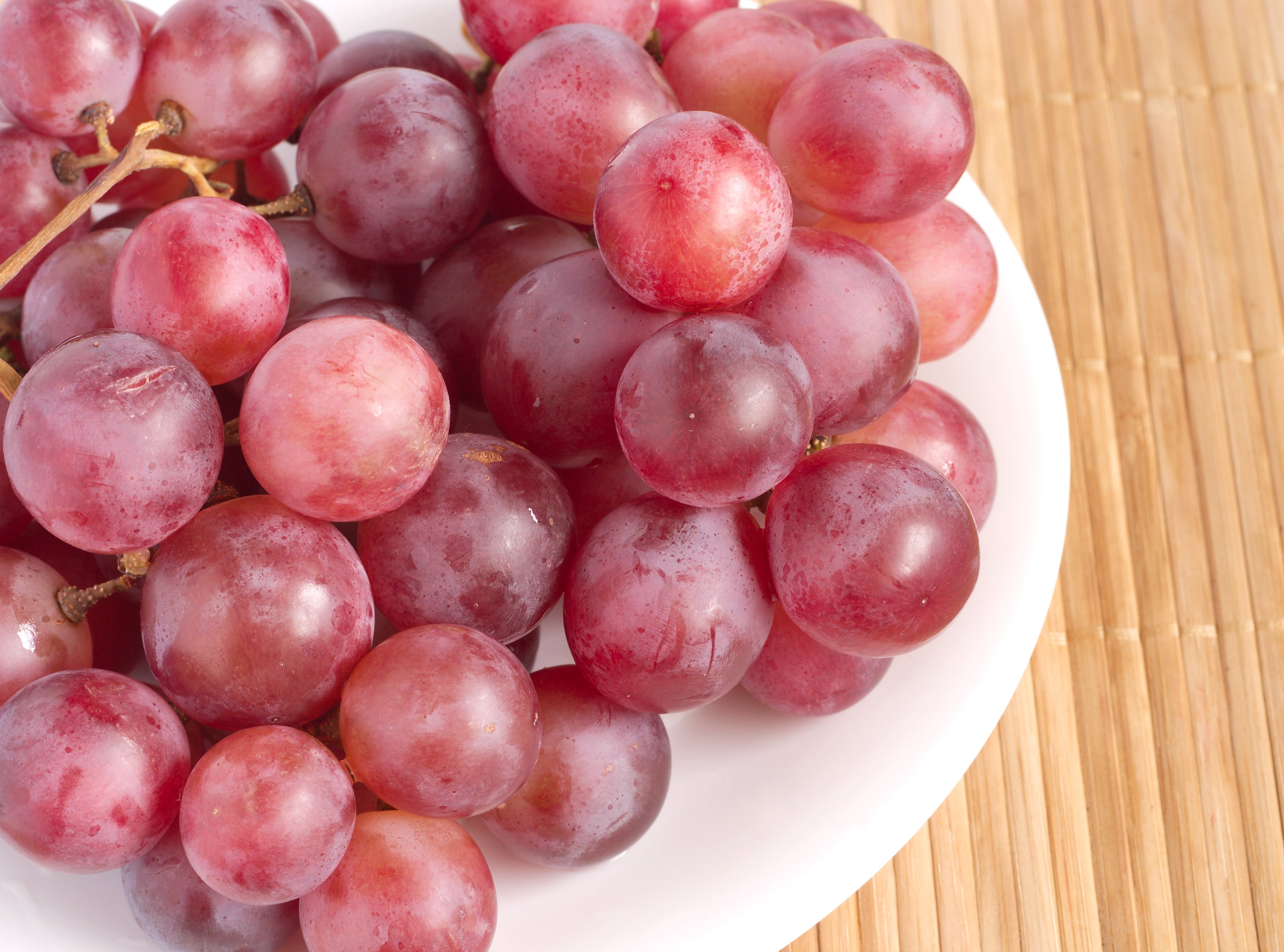 red grapes on plate on wooden table