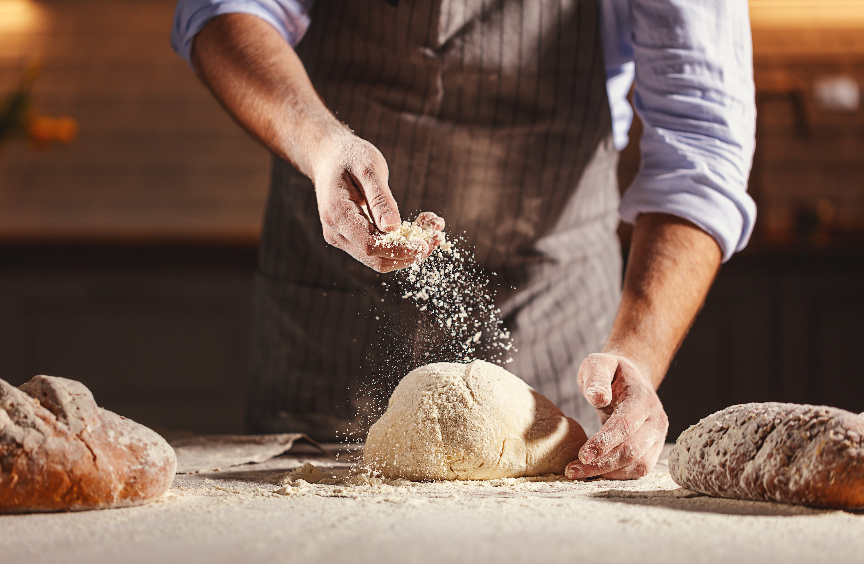 man sprinkling flour on lump of dough on workstation in between two loaves of bread