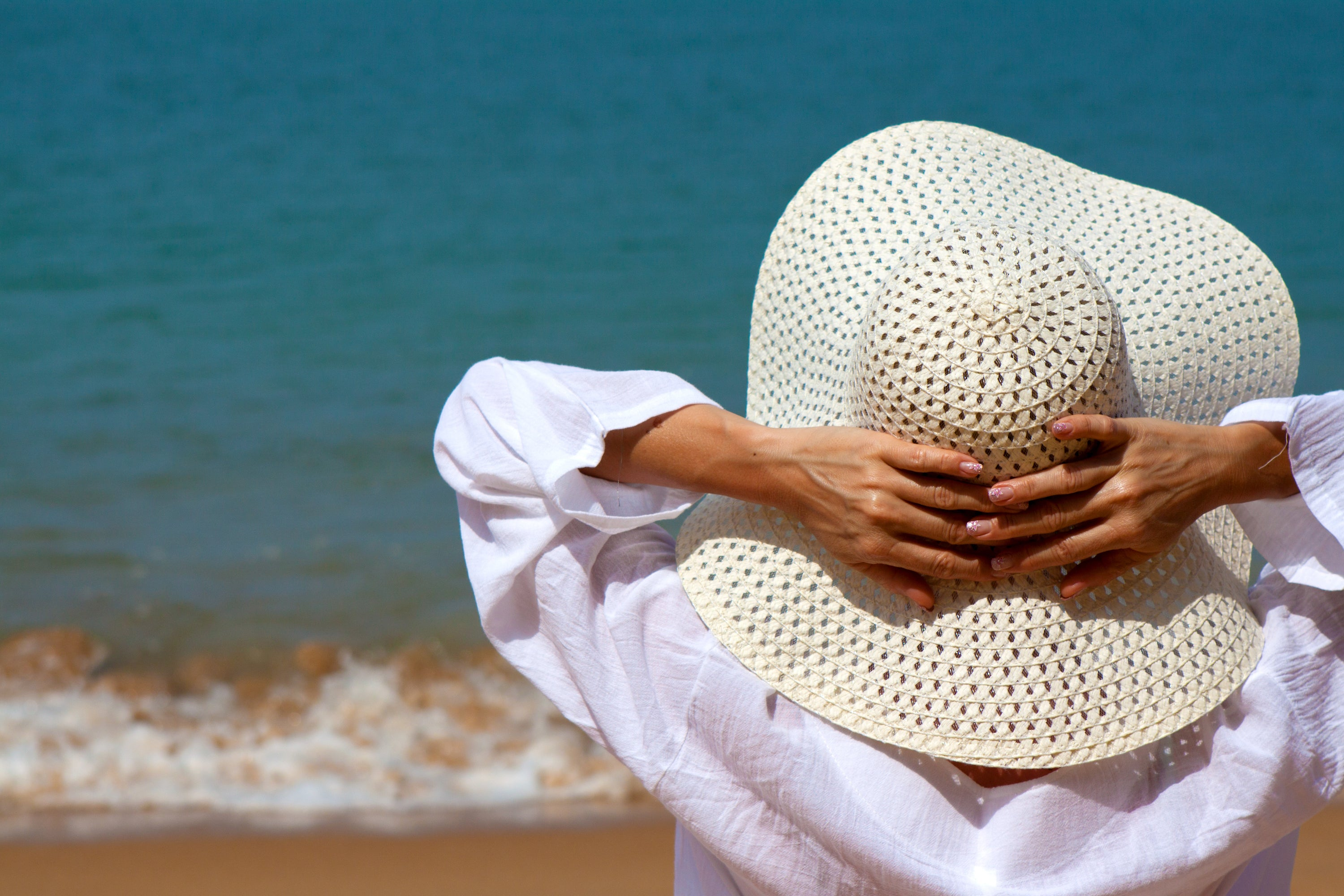 woman in linen shirt and wide-brimmed hat standing on beach looking at ocean