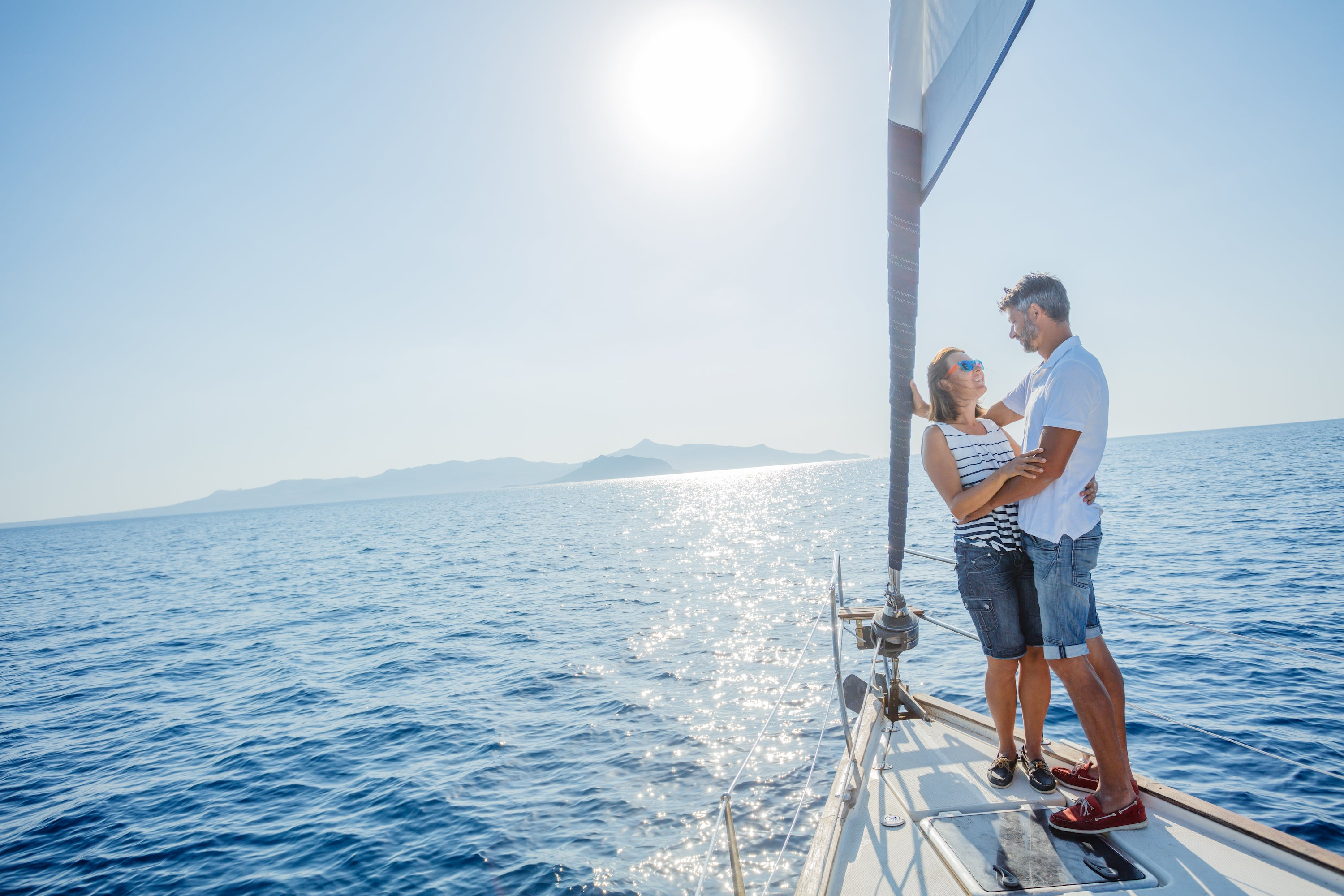 man and woman on bow of sailboat on sunny day