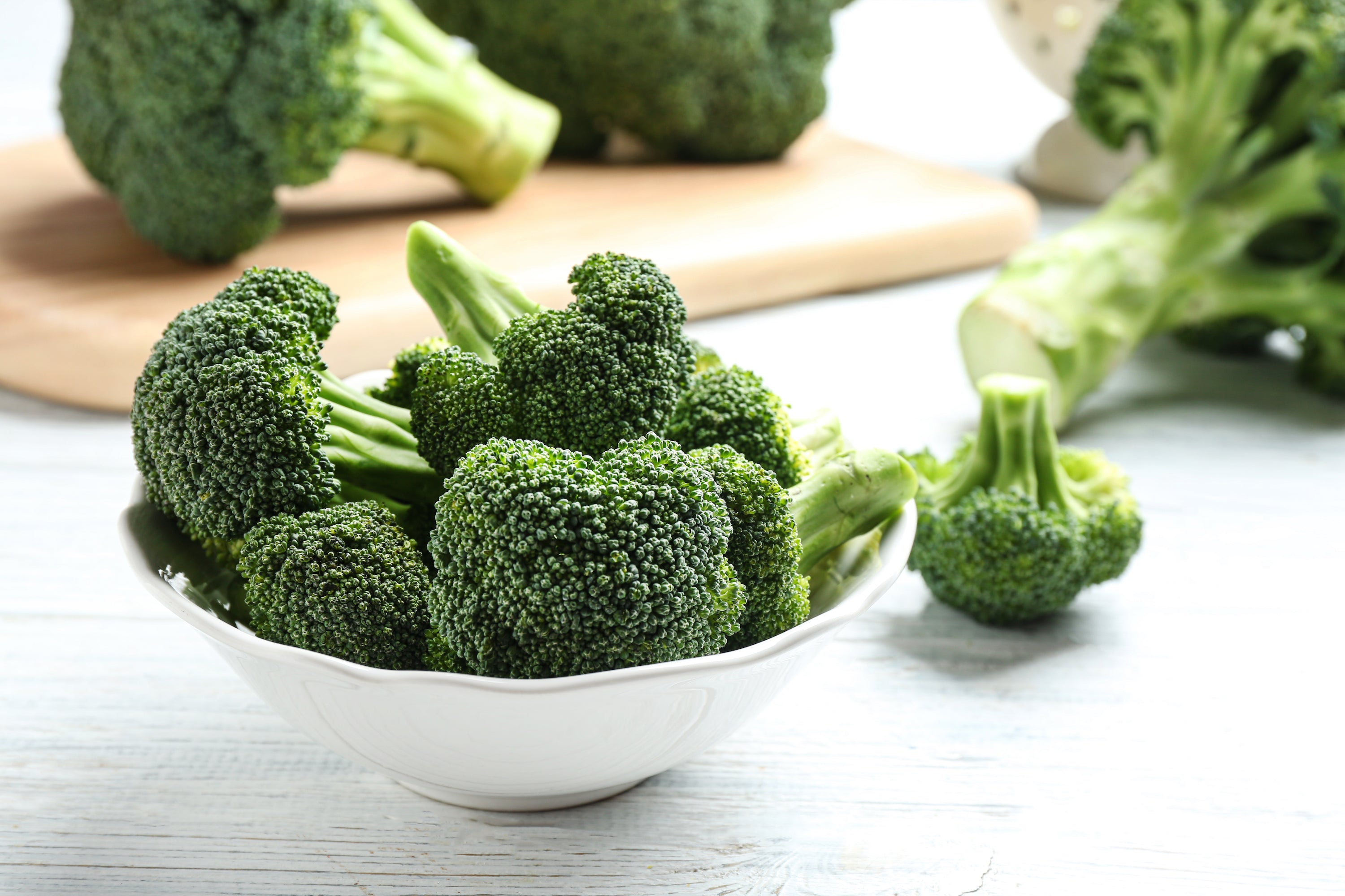 broccoli florets in bowl and on cutting board