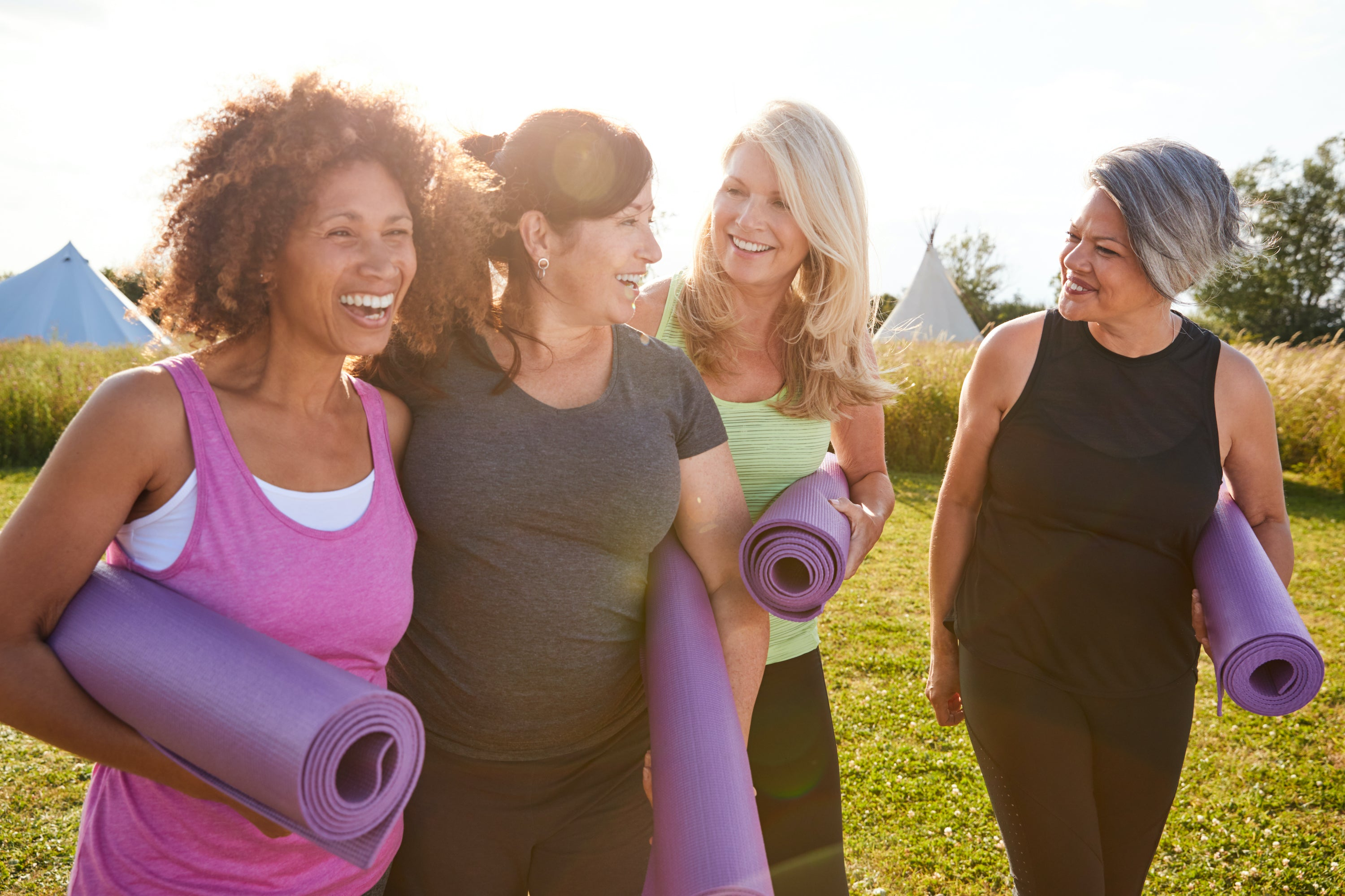 group of four middle-aged women of varying race smiling and carrying yoga mats while walking through grass field