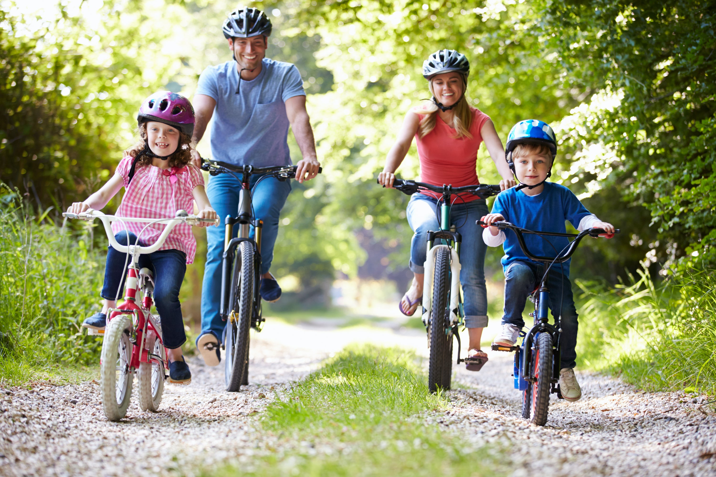 family of four on bikes wearing helmets riding down path through woods