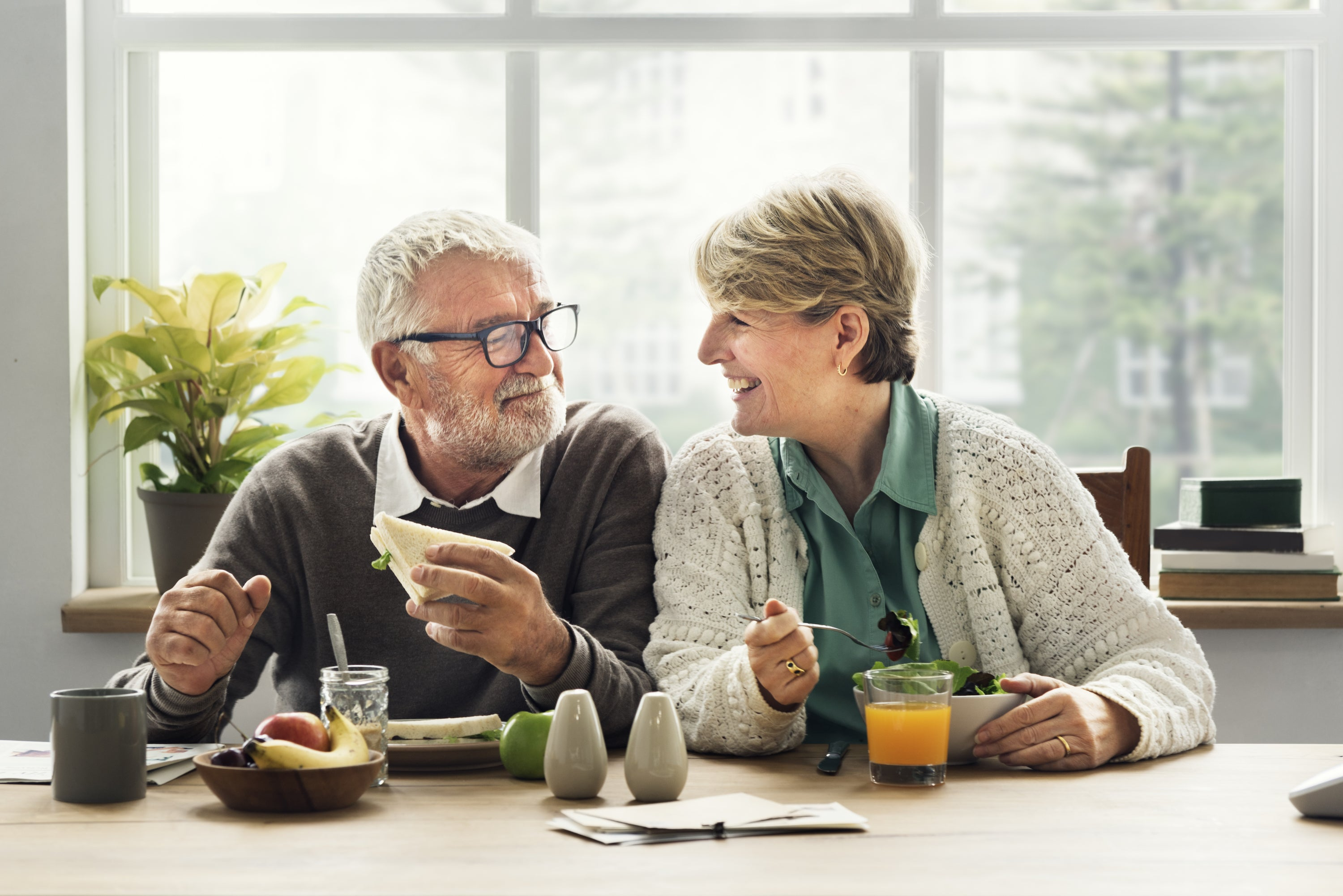 older couple smiling at each other while eating breakfast