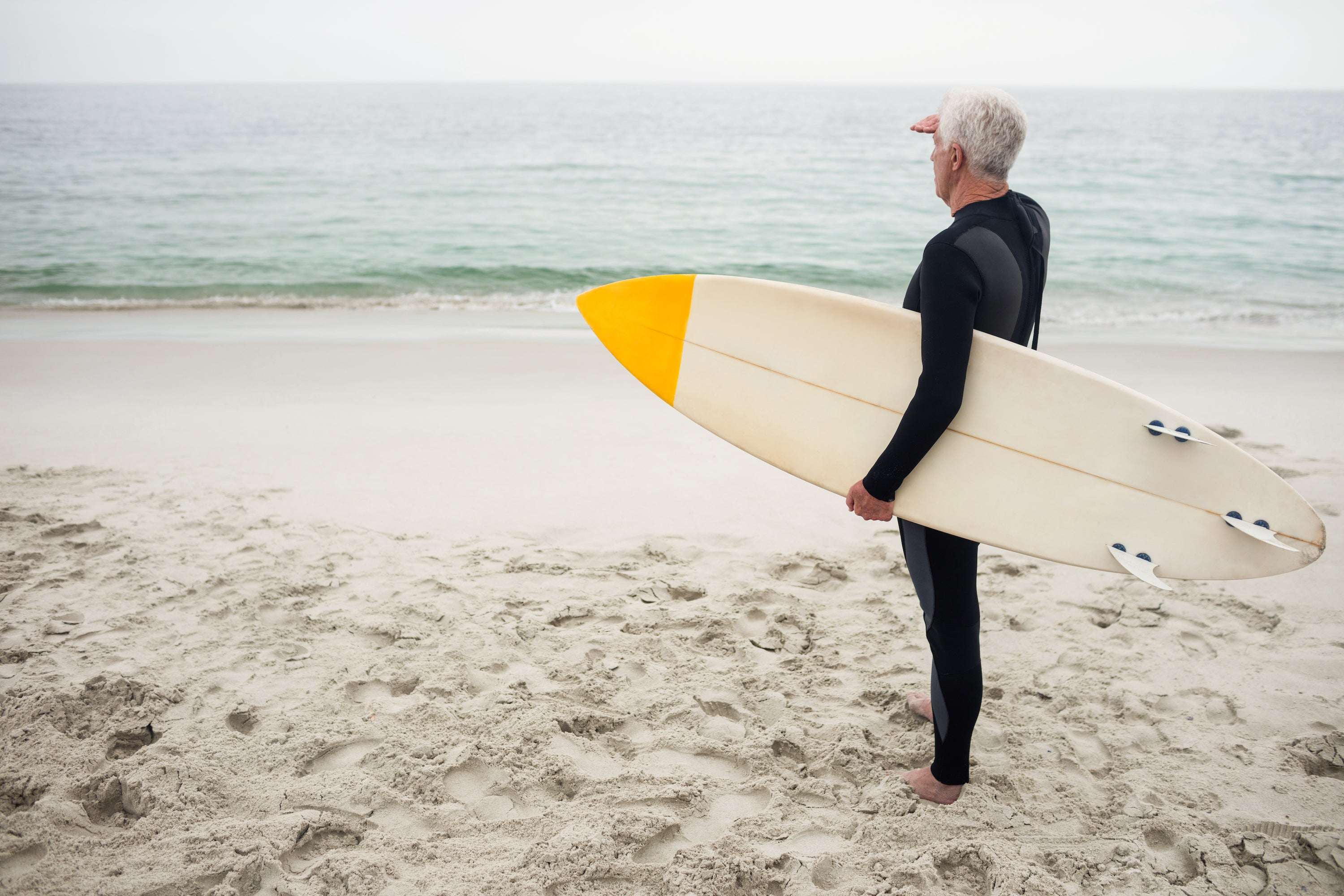 gray-haired man wearing wetsuit holding surfboard looking out to ocean