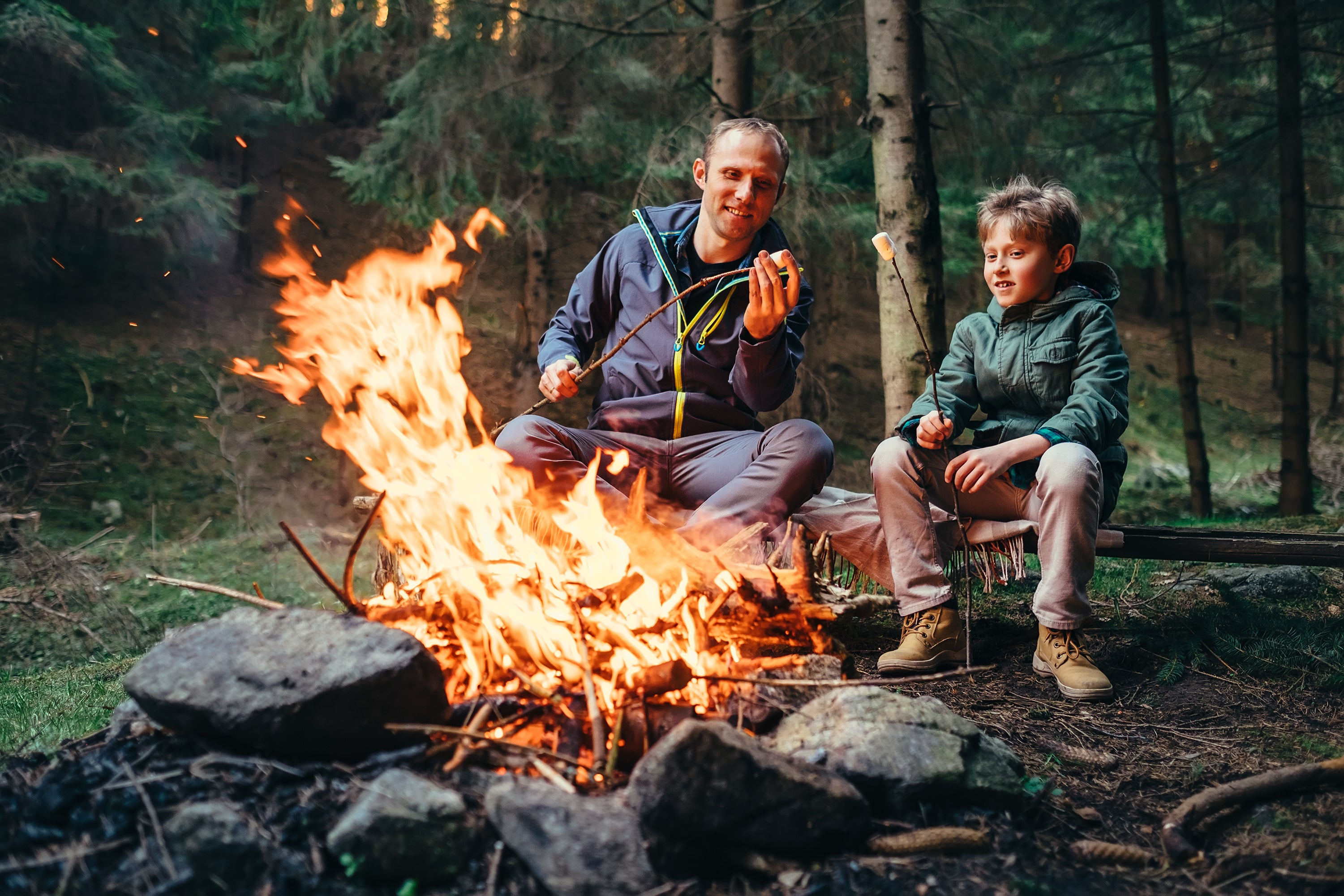 man and son sitting on log by campfire