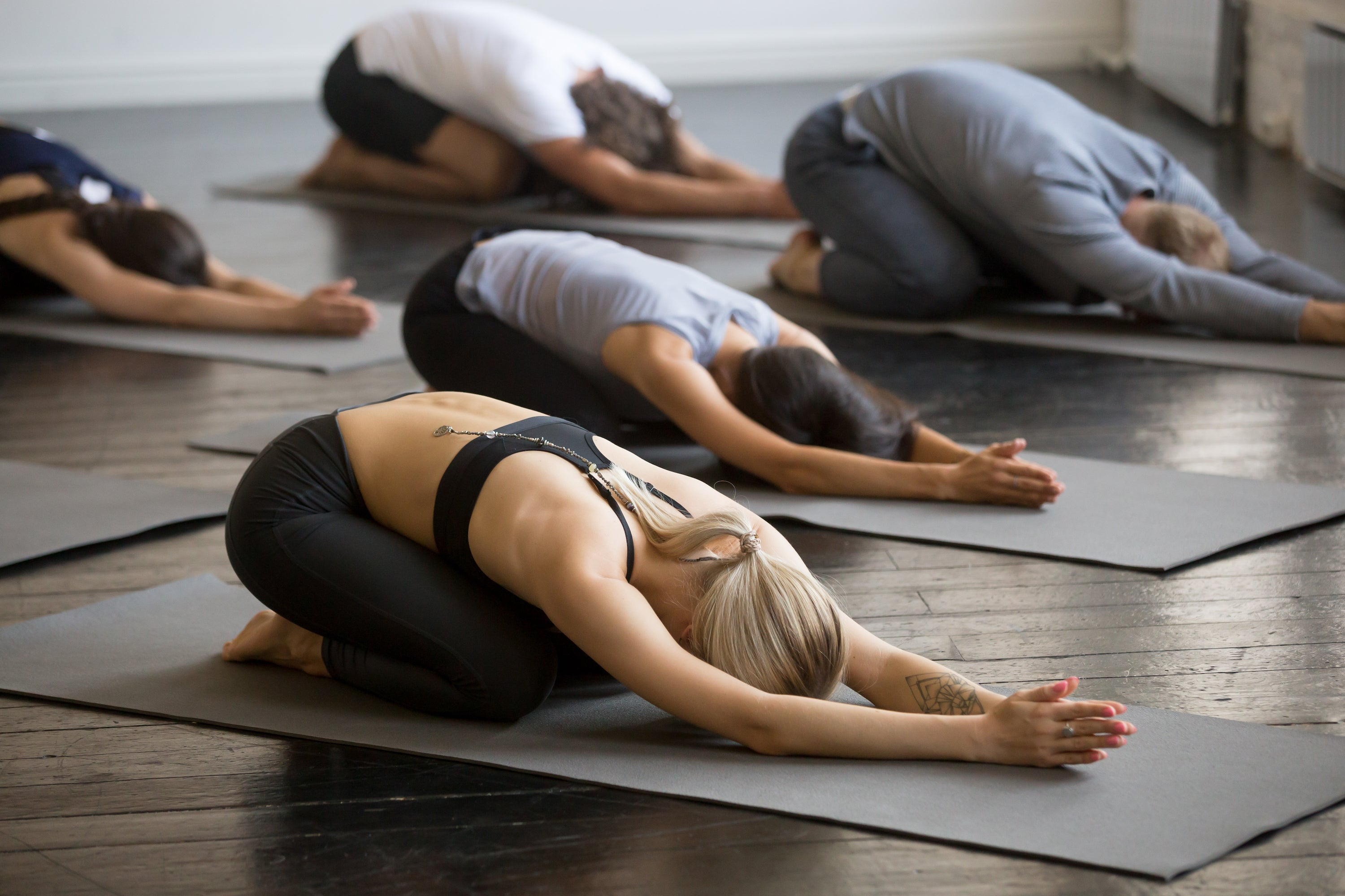 group of people in yoga studio doing child's pose on mats