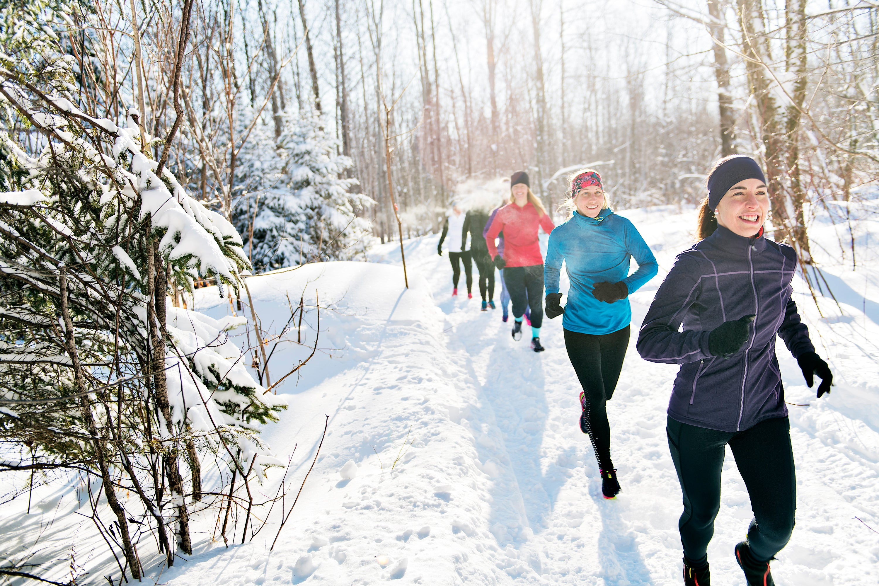 happy people in winter coats running on a trail through snowy woods