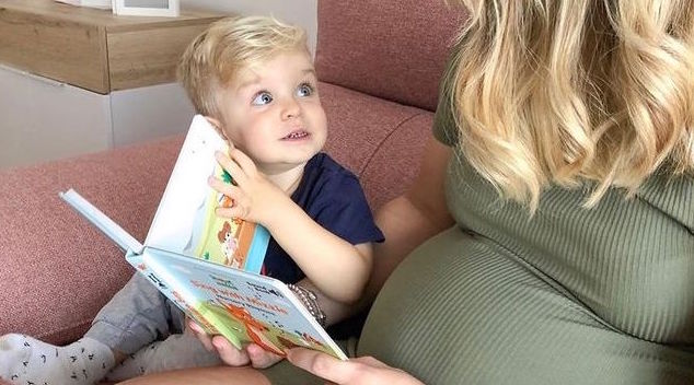 Baby is listening to mom while she is reading a Mizzie's book