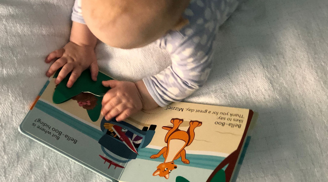 Baby reading 'At The Beach' book