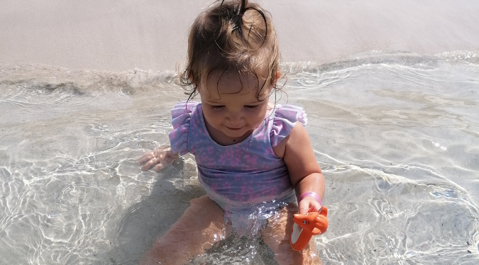 Baby playing with mini Mizzie in the water