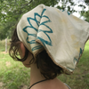 Block printed and hand dyed organic cotton bandana with yellow and green sunflower print, head covering view