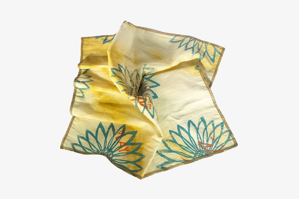 Block printed and hand dyed organic cotton bandana with yellow and green sunflower print, folded view