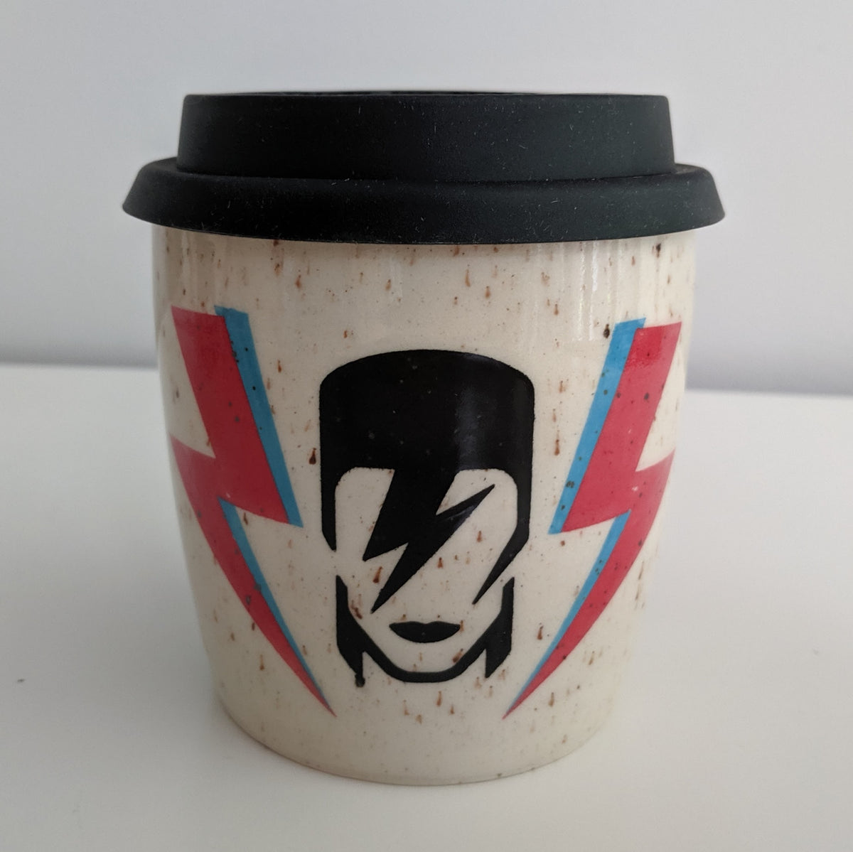 Bowie travel mug with black Ziggy Stardust icon and lightning bolts on both sides