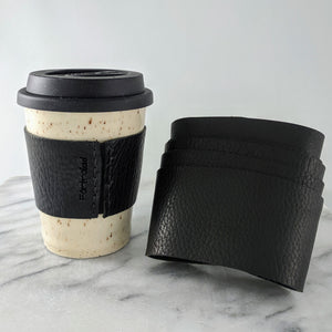 Black leather sleeves for travel mugs, used to protect your hand from the warm ceramic mug during use.